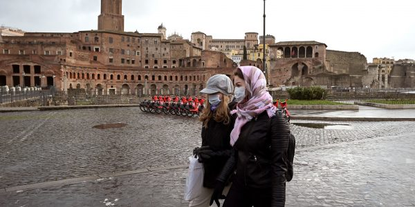 Two women wearing protective masks walks past the Trajan Forum in Rome on March 3, 2020. - The new coronavirus has spread from China across much of the world, with Italy among the worst affected with over 2,000 people infected and 52 deaths, most in the country's northern Lombardy region. (Photo by Vincenzo PINTO / AFP) (Photo by VINCENZO PINTO/AFP via Getty Images)